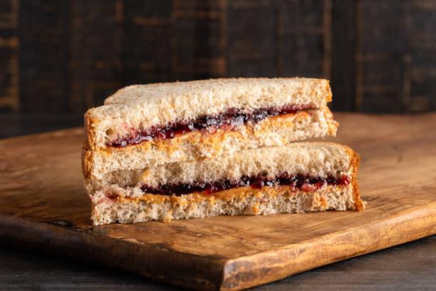 a peanut butter and grape jelly sandwich on a wooden cutting board - panino ripieno foto e immagini stock