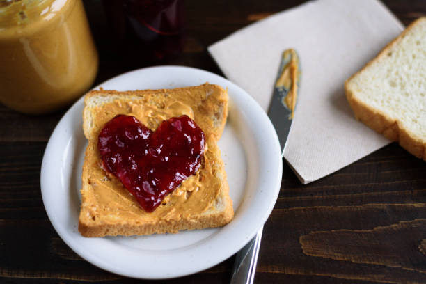 peanut butter and heart shaped jelly sandwich - spargere foto e immagini stock