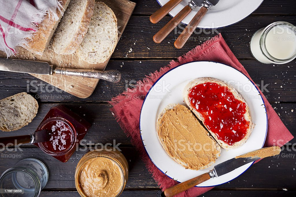 Peanut butter and jelly sandwich on a rustic table stock photo