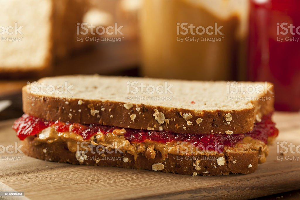 Peanut butter and jelly sandwich set on a wooden board stock photo