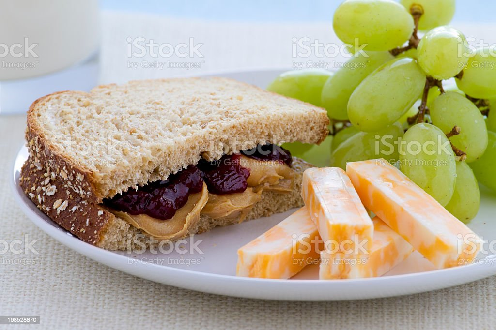 A peanut butter and jelly sandwich with cheese and grapes stock photo
