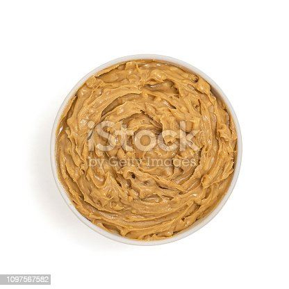 Peanut butter in bowl isolated on white background, top view.