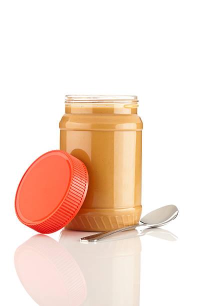 peanut butter jar with spoon isolated on white - peanutbutter bildbanksfoton och bilder