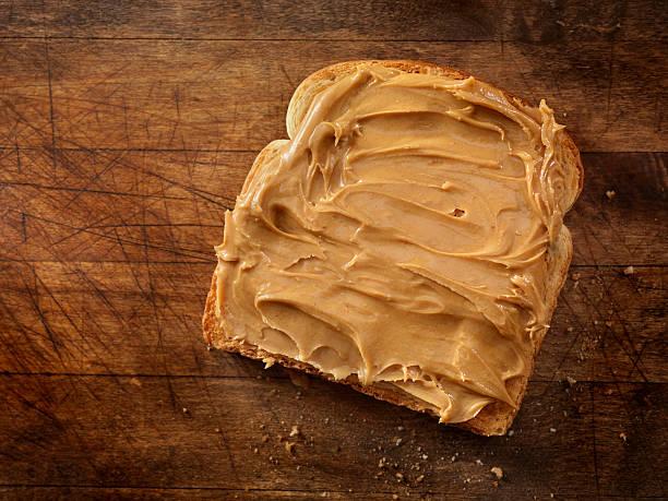 peanut butter on toast - pindakaas stockfoto's en -beelden
