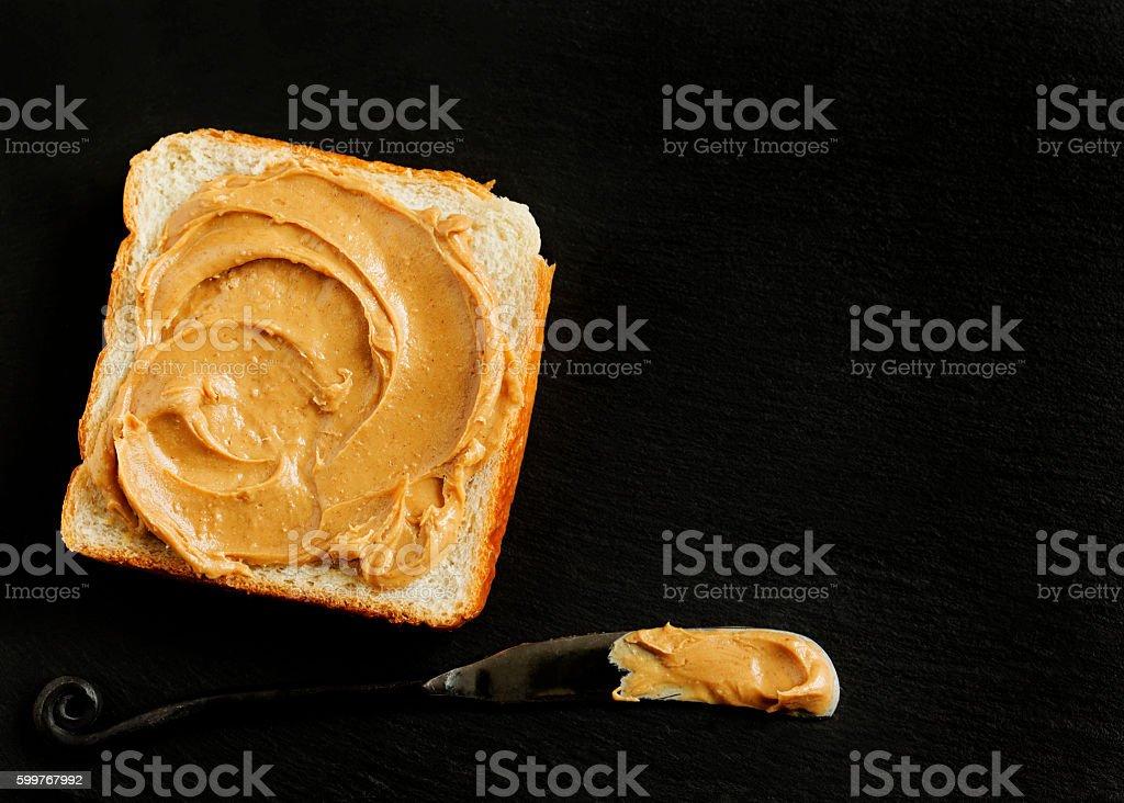 Peanut butter sandwich on black backgrpund with copy space stock photo