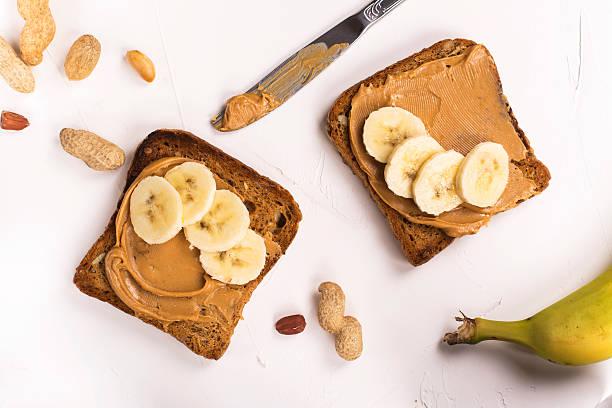peanut butter sandwiches on white kitchen table - pindakaas stockfoto's en -beelden