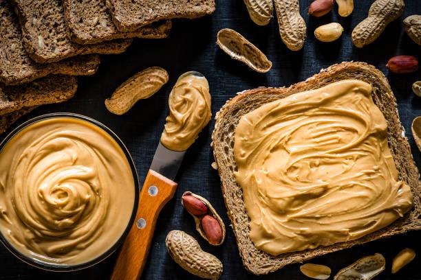 pindakaas verspreid over een schijfje brood - pindakaas stockfoto's en -beelden