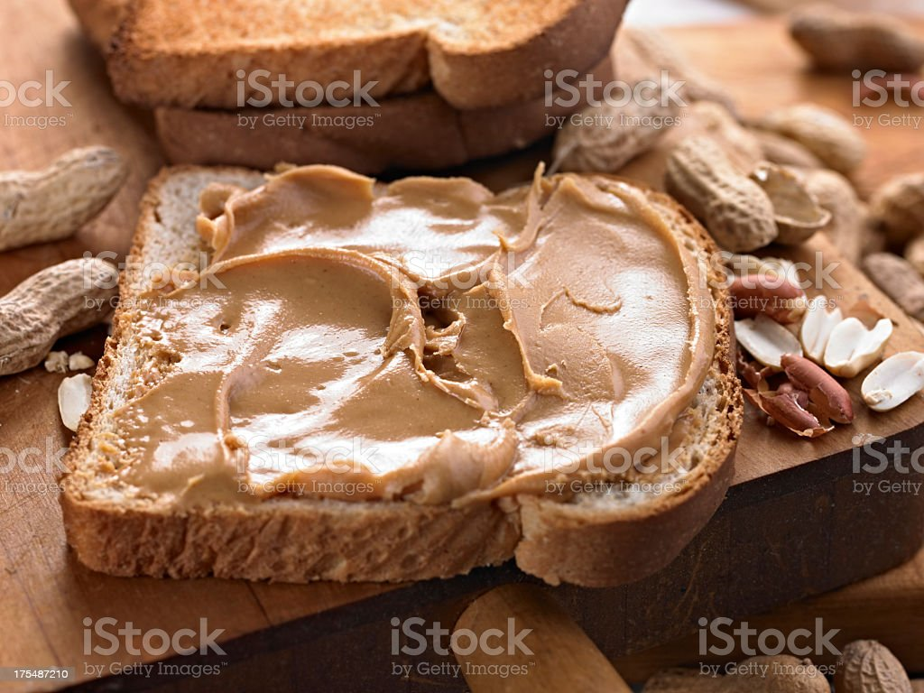 Peanut butter toast on table surrounded by peanuts shells stock photo