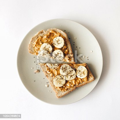 Peanut butter chia seed banana toast for breakfast on a white background, healthy snack, top view