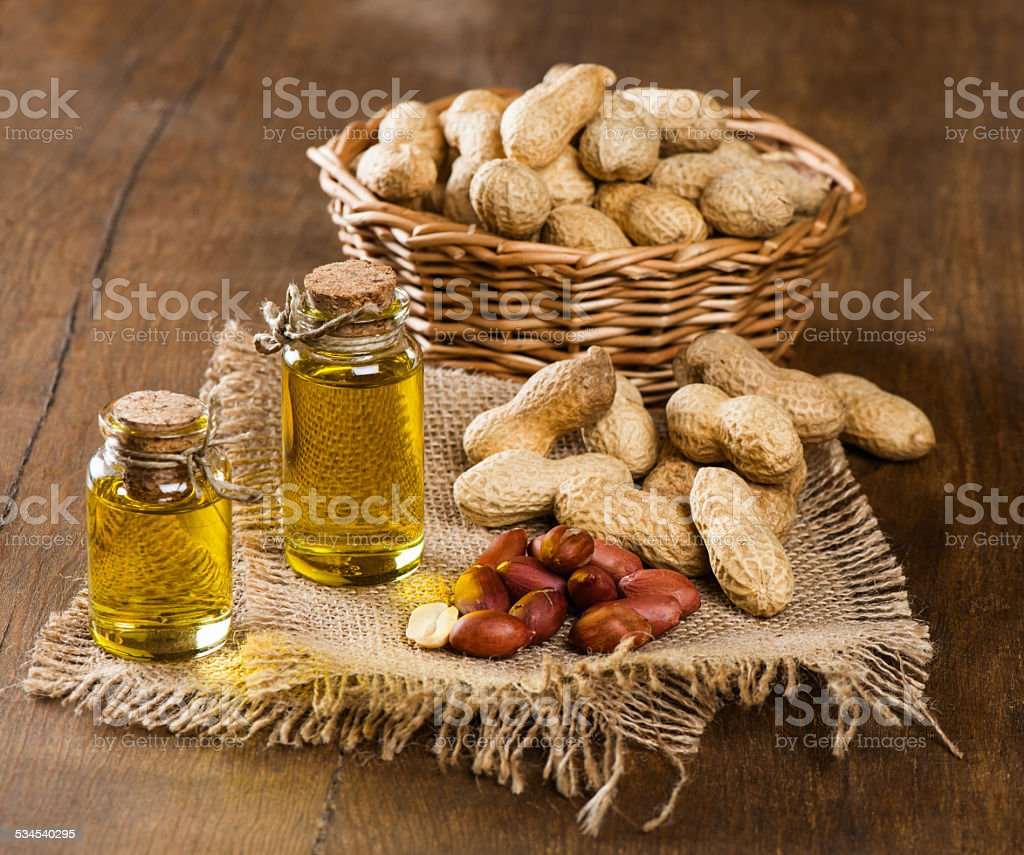 peanut oil and nuts on a wooden table stock photo