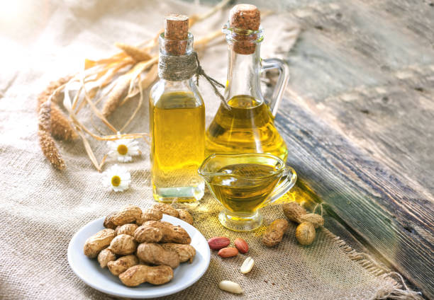 Peanut oil and peanuts on a wooden table on a sunny day stock photo