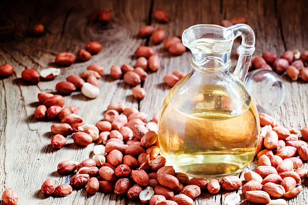 Peanut oil in a glass jar, raw peanuts stock photo
