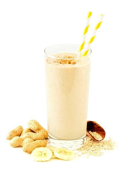 peanut-butter banana oat smoothie with scattered ingredients over white - peanutbutter bildbanksfoton och bilder