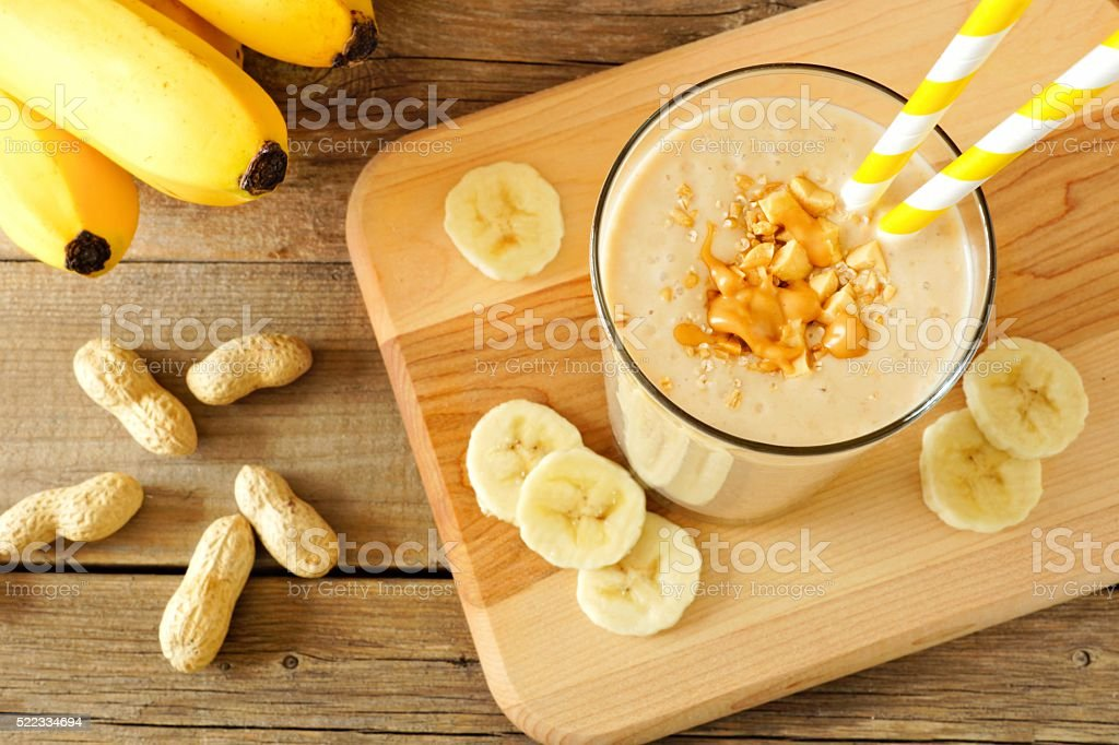 Peanut-butter banana oat smoothie with straws, on wood stock photo