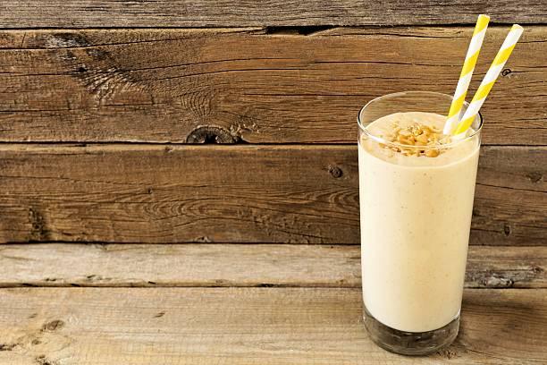 peanut-butter banana oat smoothie with straws over rustic wood - peanutbutter bildbanksfoton och bilder