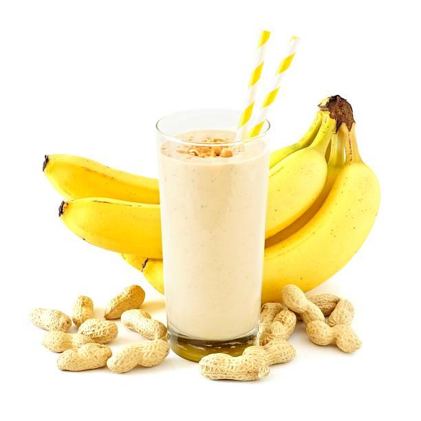 peanut-butter banana smoothie with scattered ingredients over white - peanutbutter bildbanksfoton och bilder