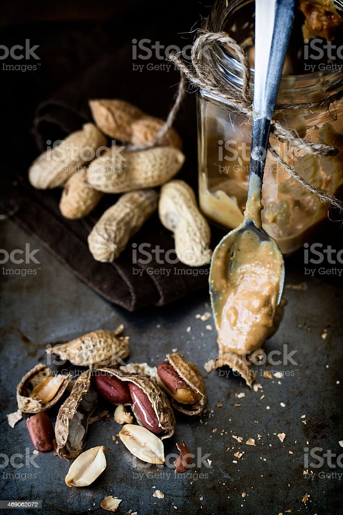 Peanuts and jar of homemade peanut butter. stock photo