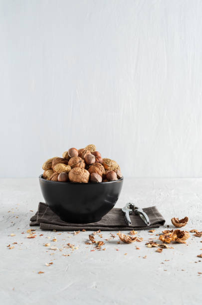 Peanuts and nuts in a bowl on a delicate grey background - foto stock