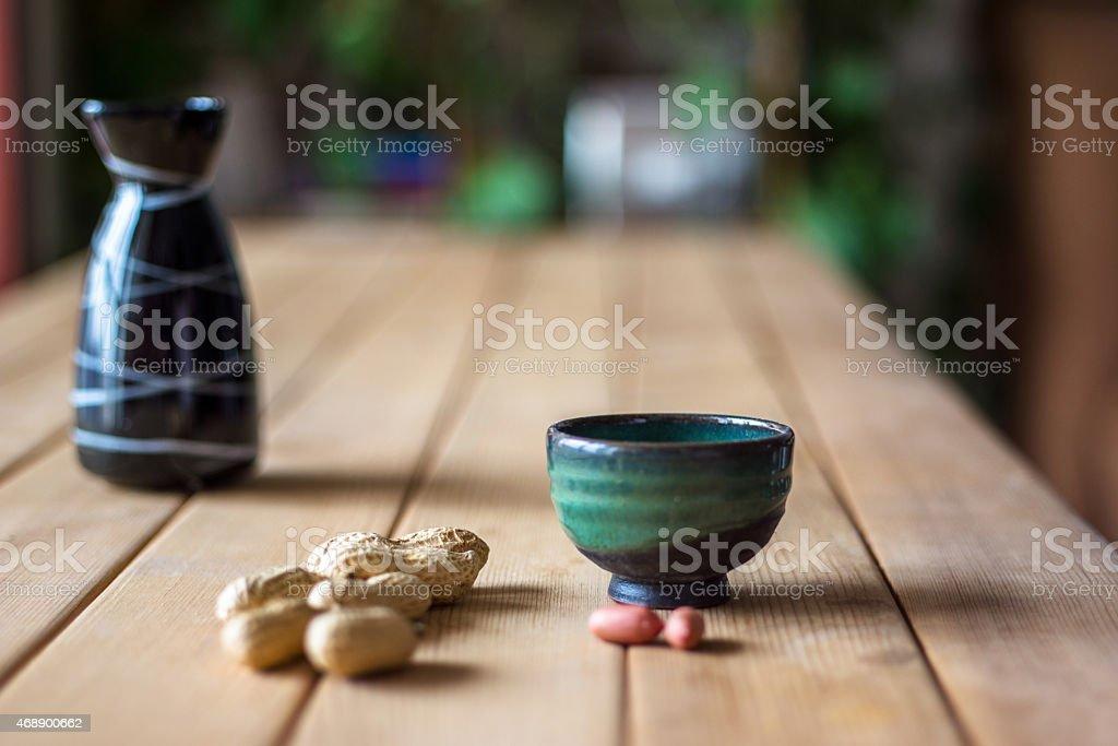 peanuts und Weinflasche auf Holztisch - Lizenzfrei 2015 Stock-Foto