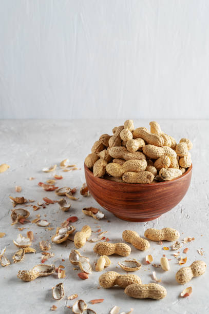 Peanuts in a wooden bowl on a delicate grey background - foto stock