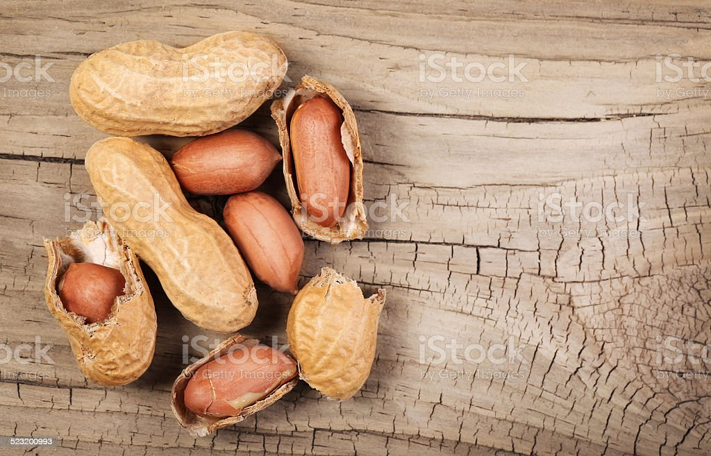 Peanuts in shells on wood background stock photo