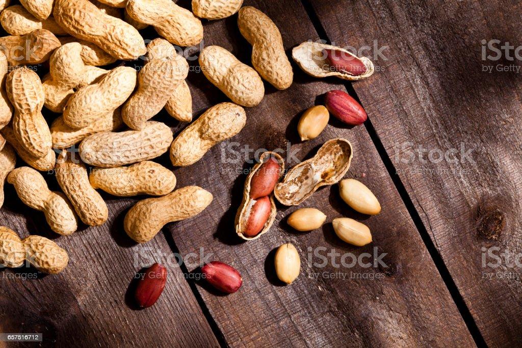 Peanuts on rustic wood table stock photo