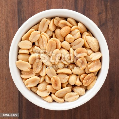 Top view of white bowl full of peanuts
