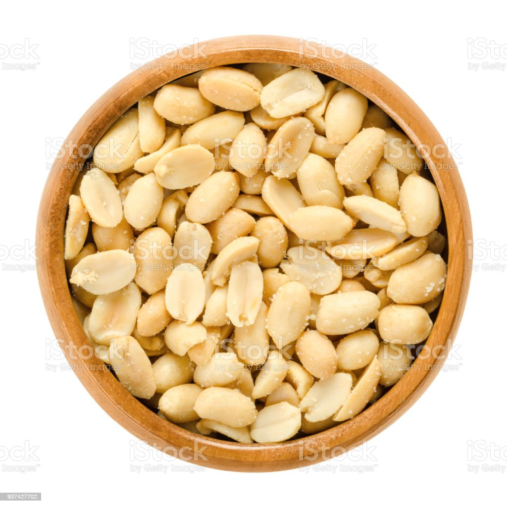 Peanuts, roasted and salted, in wooden bowl, over white stock photo