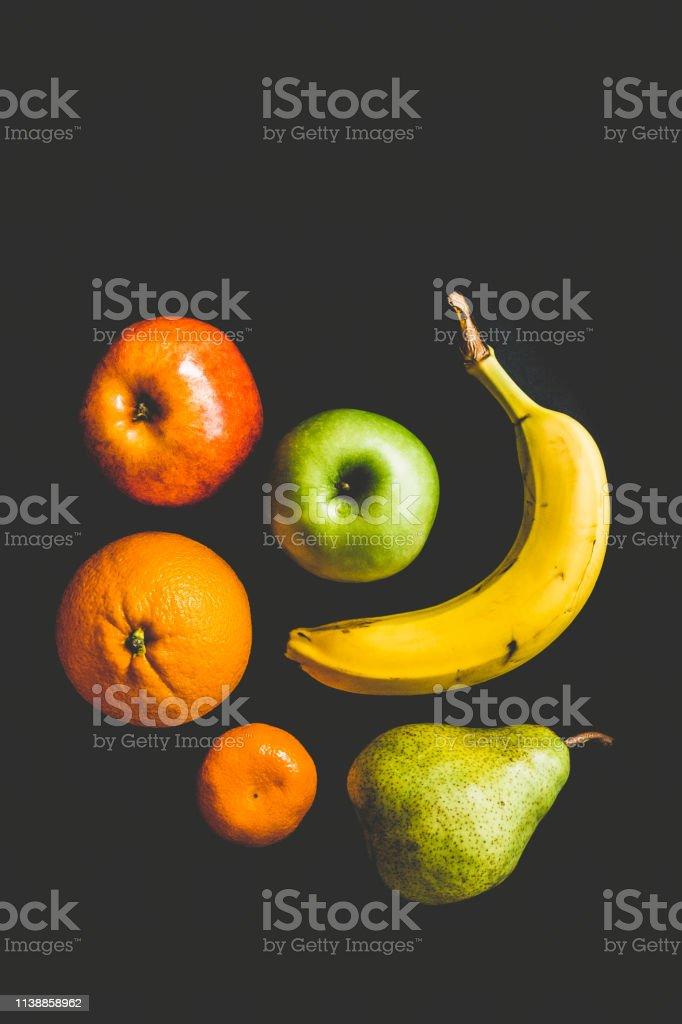 Yellow banana, green apple, red apple, orange fruit, green pear and...