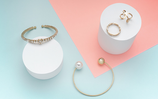 istock Pearl and diamonds golden bracelets and golden rings on pastel color background 1172051028