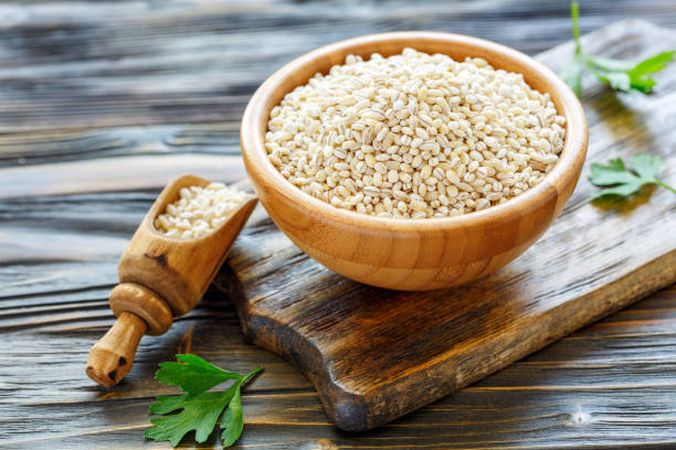 Pearl barley in a wooden bowl and scoop with barley. stock photo