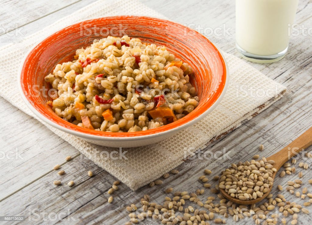 Pearl barley porridge with vegetables in a ceramic dish stock photo