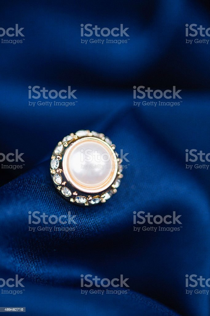 Pearl earring on rich sapphire blue satin background stock photo