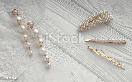 Pearl golden earrings pair and hairpin set on wooden textured background
