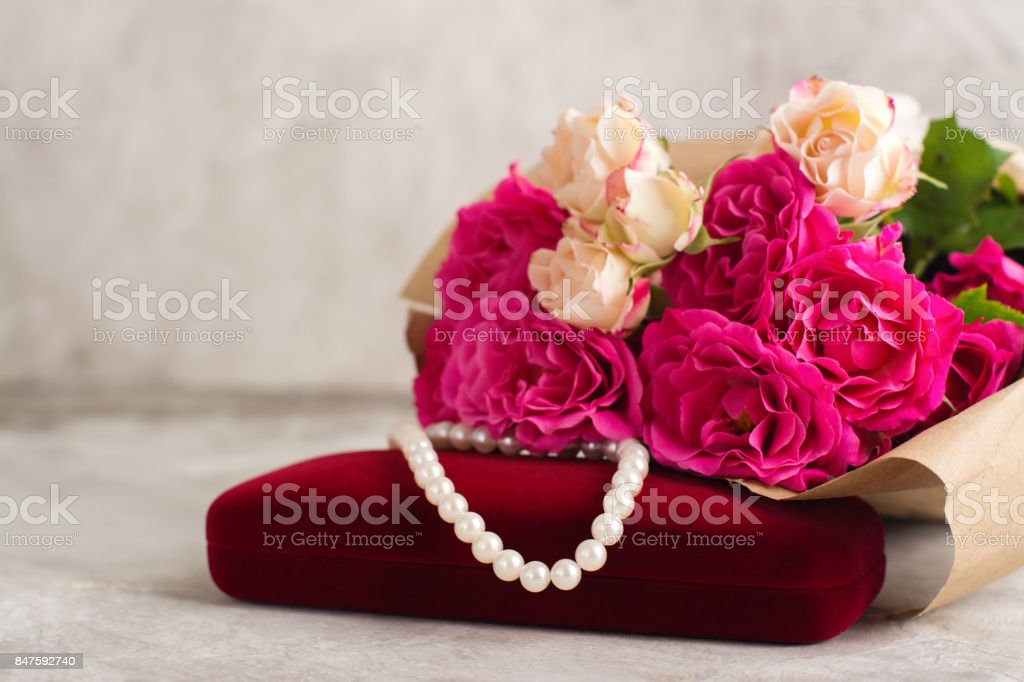 Pearl necklace and roses bouquet stock photo