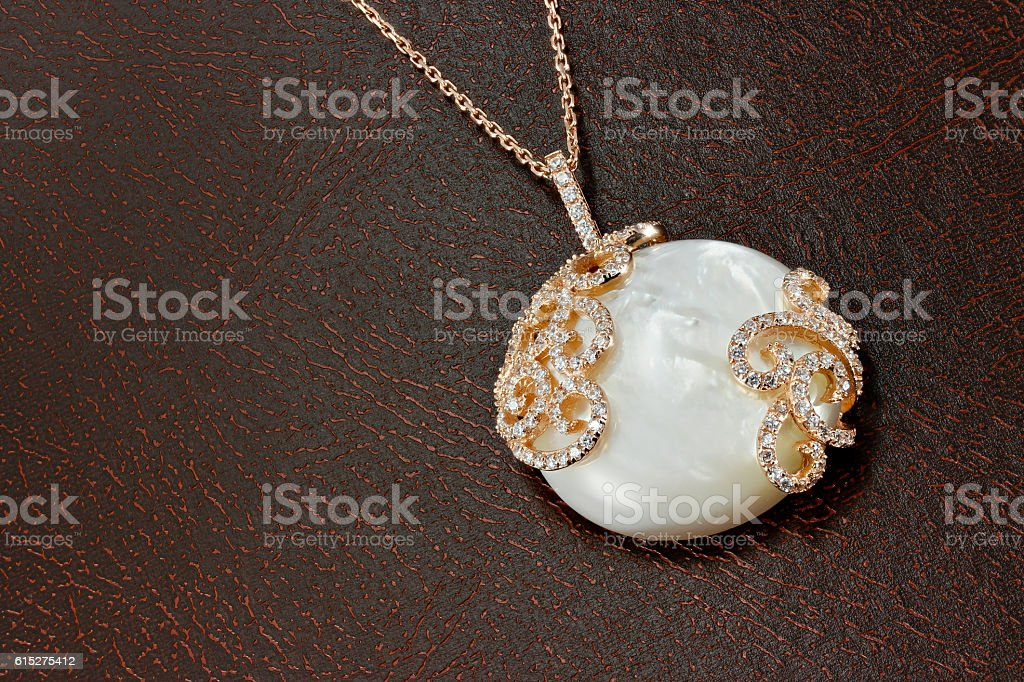 Pearl pendant on leather surface stock photo