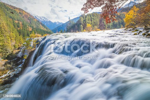 Pearl Shoals Waterfall among scenic wooded mountains and evergreen forest in Jiuzhaigou nature reserve