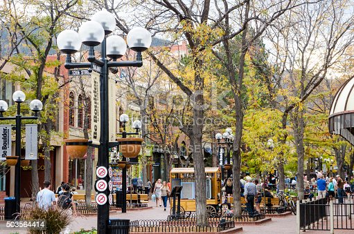 Boulder, Colorado, USA - October 18, 2015: People gather on Pearl Street on a beautiful Fall evening. The Pearl Street Mall, also referred to as Pearl Street, or Downtown Boulder, is a four block pedestrian mall in Boulder, Colorado. The pedestrian area stretches from 11th Street to 15th Street along Pearl Street and is home to a number of businesses and restaurants as well as the Boulder County Courthouse. The Pearl Street Mall is a popular destination for tourists visiting Boulder and for students attending the nearby University of Colorado Boulder. The mall hosts a blend of locally-owned businesses and national chain stores and restaurants. It is also home to much of Boulder's nightlife. During the summer months, Pearl Street Mall is the stage for a number of street performers, including musicians. It is also a favorite gathering spot for many of Boulder's homeless people.