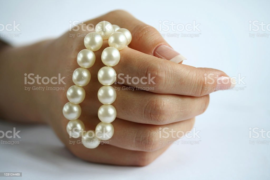 Pearl string in a female hand, over white stock photo