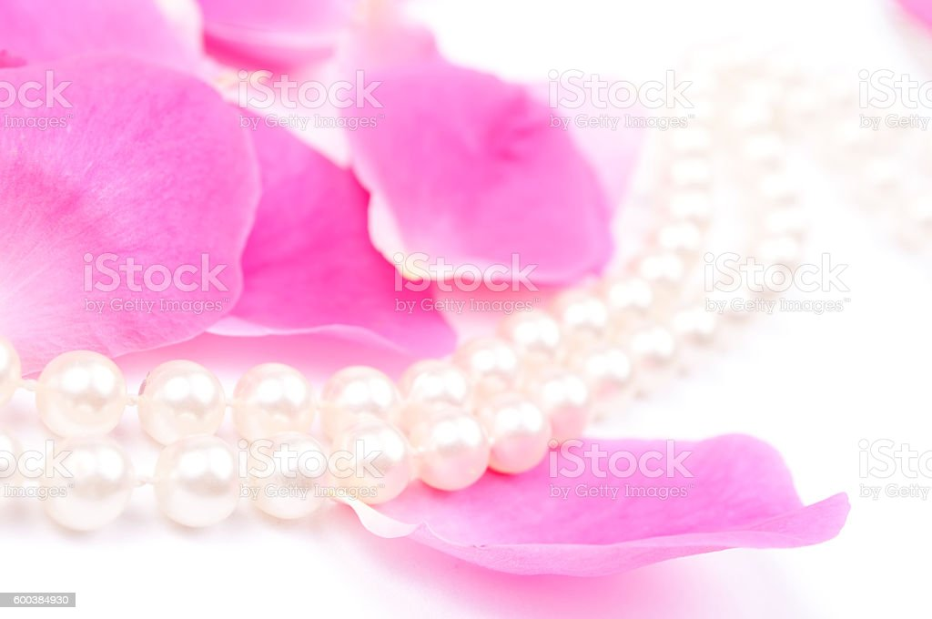 Pearls necklace on a pink Rose petals stock photo