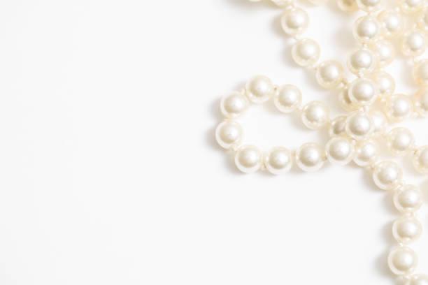 pearls white background on a necklace - ожерелье стоковые фото и изображения