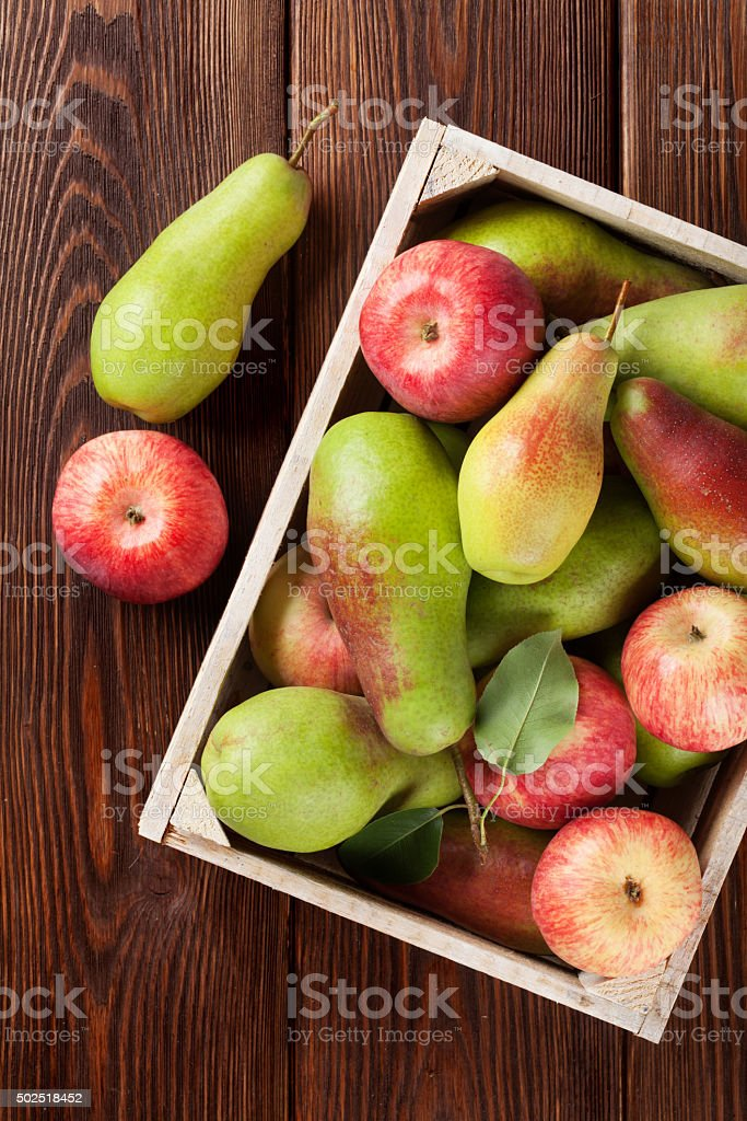 Pears and apples in wooden box on table stock photo