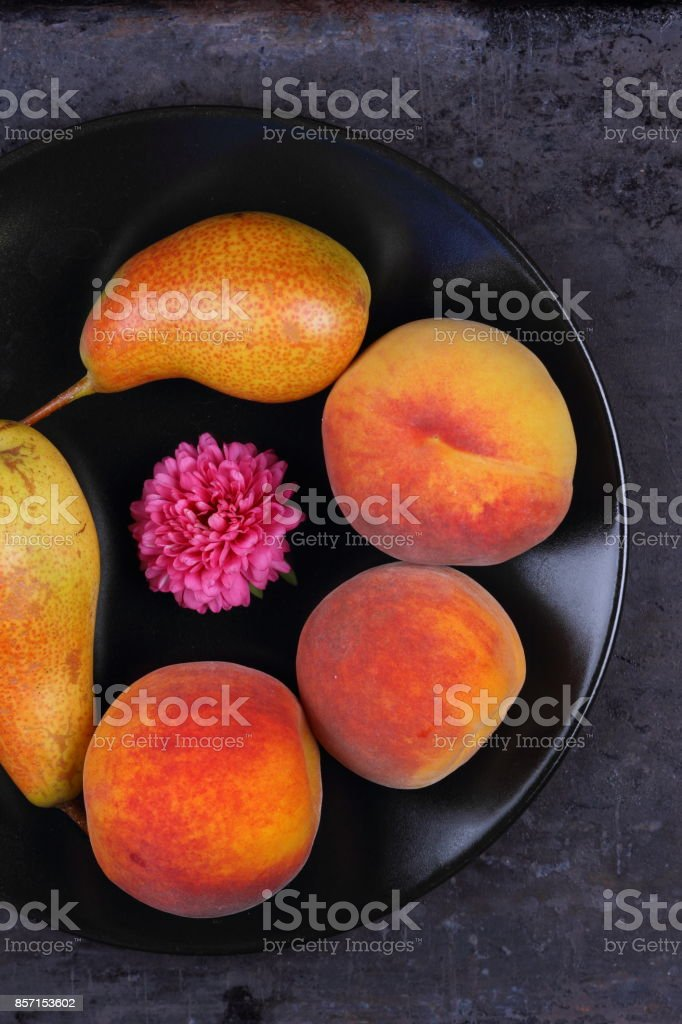 Pears and peaches on a black plate in retro style stock photo