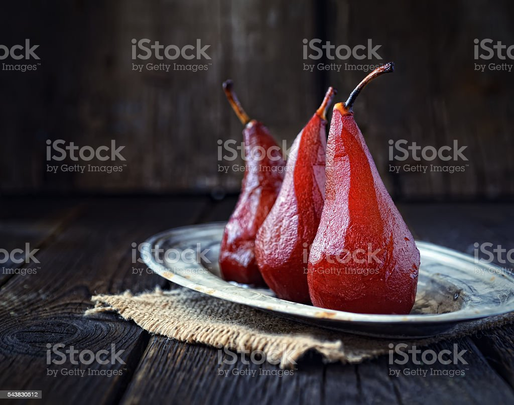 pears in red wine on a vintage plate stock photo