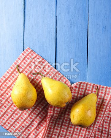 Three ripe pears with tablecloth on blue wooden background. Top view. Copy space