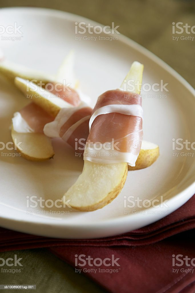 Pears wrapped in proscuitto in plate, close-up, elevated view photo libre de droits