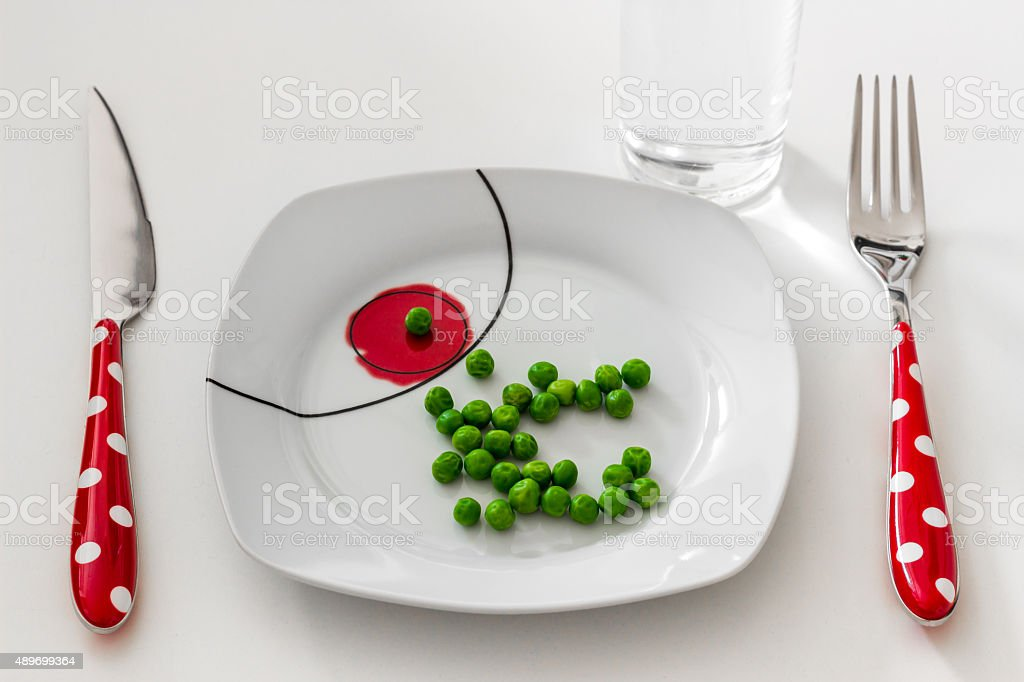 Peas on a plate, a glass of water, dieting concept stock photo