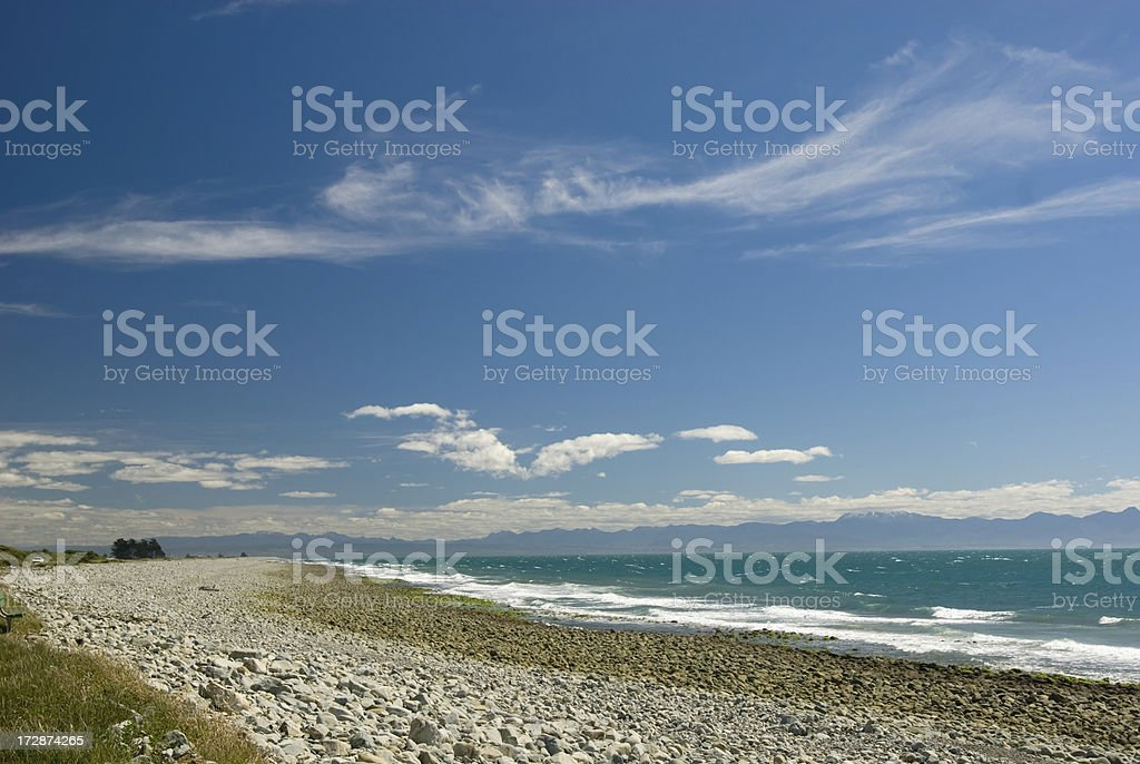Pebble beach, distant mountains and cloudscape stock photo