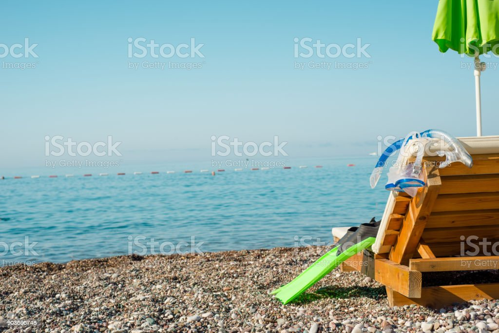 Pebble beach paradise, diving equipment and wooden beach chair stock photo