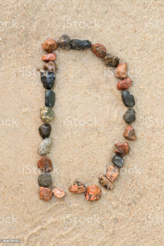 pebble d letter  on sand stock photo